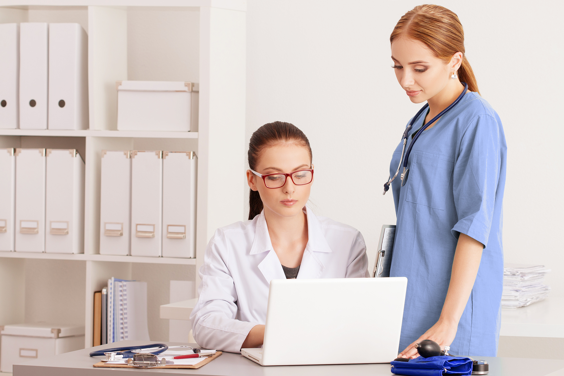 Two beautiful female medicine doctors looking at laptop monitor standing at their office. Medical and healthcare concept